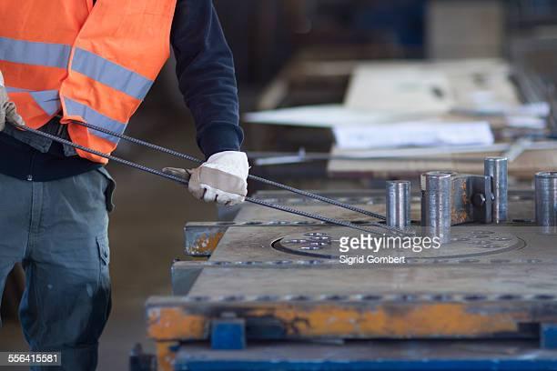 factory worker bending metal rod in concrete reinforcement factory - sigrid gombert stock-fotos und bilder