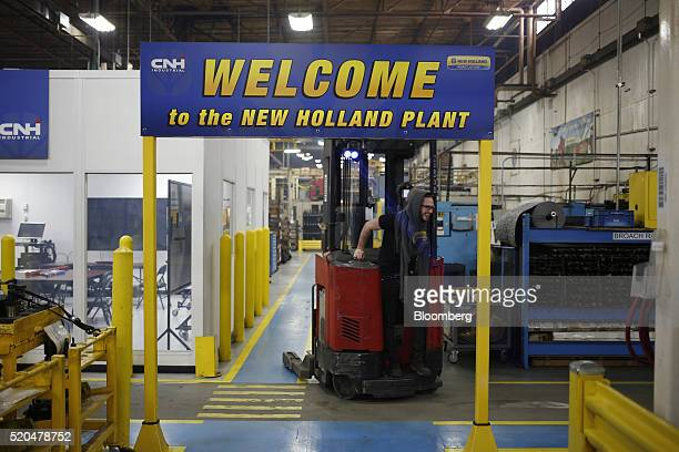 A factory worker drives a forklift through the assembly floor at the New Holland Ltd Haytools factory in New Holland Pennsylvania US on Friday April...