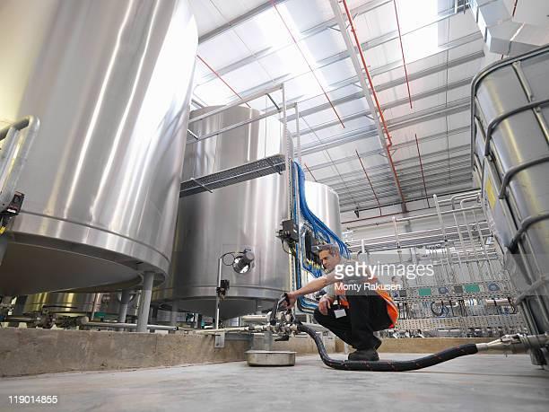 Factory worker examining storage tanks