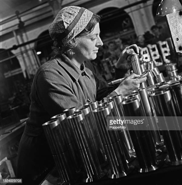 Factory worker Frances Davies uses a micrometer to measure metal component parts for tanks at a Ministry of Supply factory in England during World...