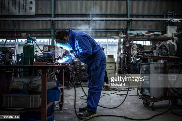 factory worker grinding metal pieces - effort stock pictures, royalty-free photos & images