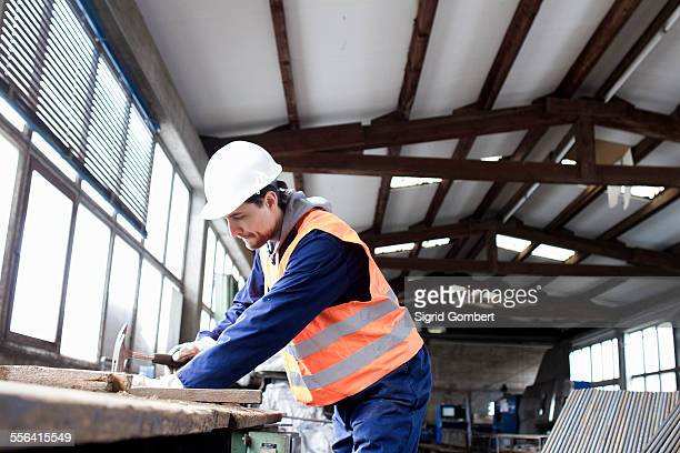 Factory worker hammering on workbench in concrete reinforcement factory