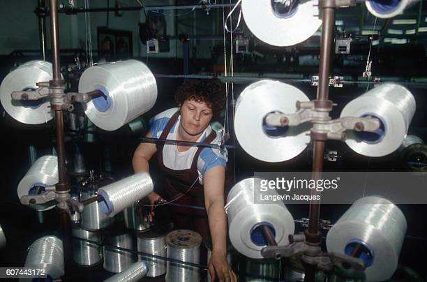 Factory worker handles spools of materials at the Terom synthetic fiber factory in Iasi in Romanian Moldavia.