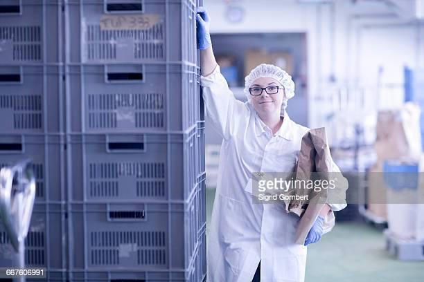factory worker holding packaging looking at camera smiling - sigrid gombert - fotografias e filmes do acervo