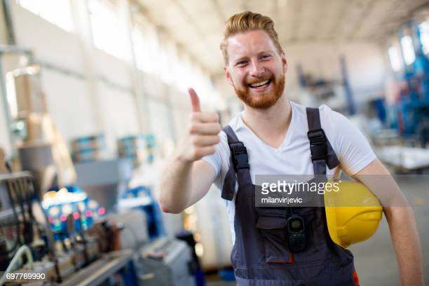 Factory worker holding thumbs up