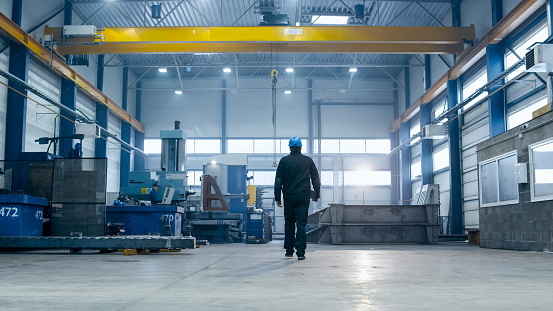 Factory worker in a hard hat is walking through industrial facilities. 838527622
