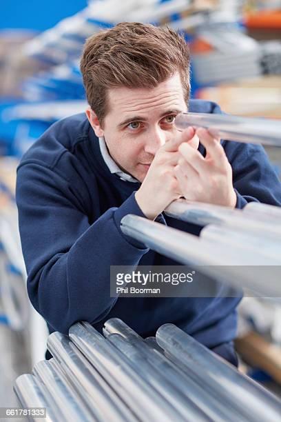 Factory worker inspecting metal rods in roller blind factory