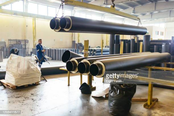 factory worker lifting the big pipe with crane - crane construction machinery stock pictures, royalty-free photos & images