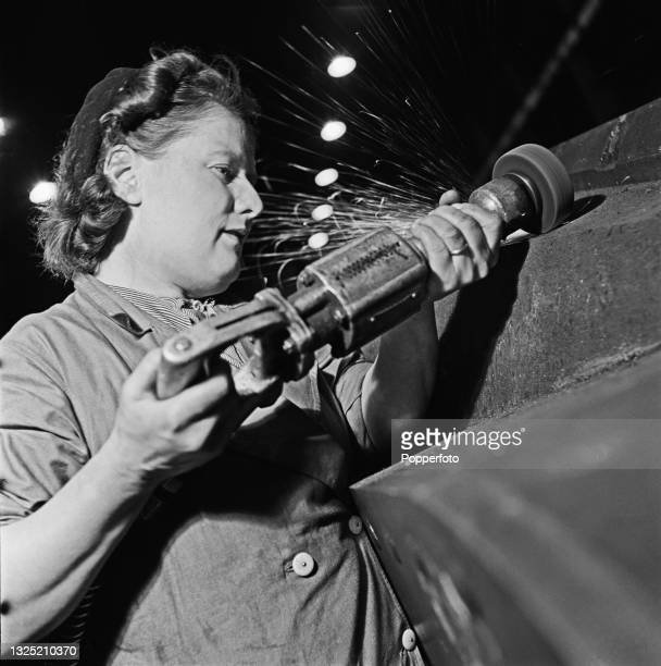 Factory worker Lucy O'Brien uses a portable grinder on the chassis of a partially assembled tank under construction at a Ministry of Supply factory...