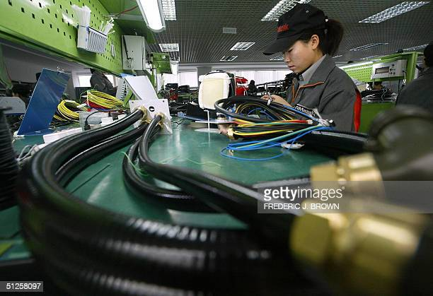 A factory worker makes parts at a joint venture Chinese and Japanese electronics firm manufacturing digitally controlled machinery for automotive...