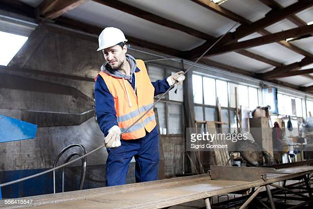 factory worker moving steel rod at concrete reinforcement factory - sigrid gombert fotografías e imágenes de stock