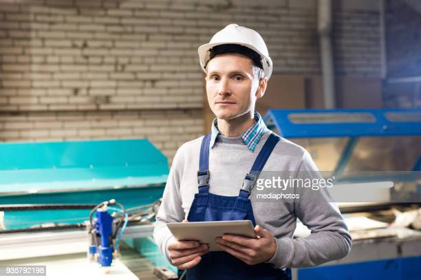 Fabrikarbeiter, die Mieter Maschine mit Tablet-PC in Betrieb