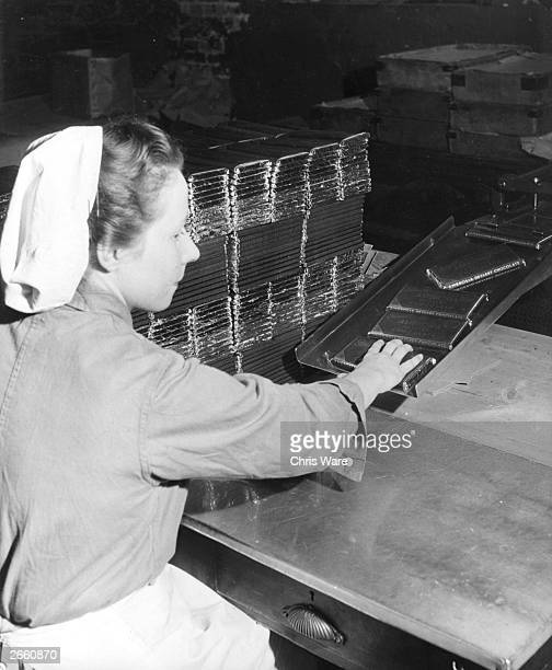 A factory worker packing bars of Ambrosia dessert chocolate in preparation for the lifting of the chocolate ration