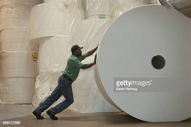 Factory Worker Pushing Roll of Paper