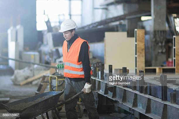 factory worker pushing wheelbarrow in concrete reinforcement factory - sigrid gombert stock pictures, royalty-free photos & images