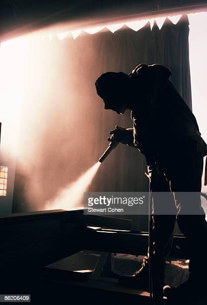 Factory worker sandblasting industrial equipment