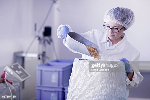 factory worker scooping food into sack - sigrid gombert stock-fotos und bilder