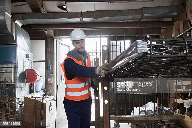 factory worker selecting steel mesh in concrete reinforcement factory - sigrid gombert fotografías e imágenes de stock