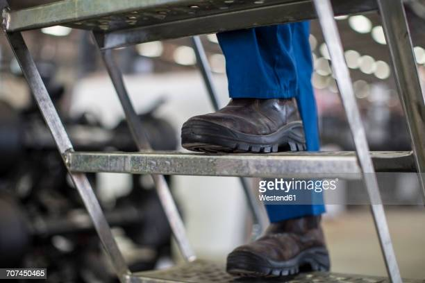 Factory worker standing on ladder, close up