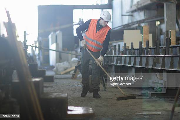 factory worker sweeping up in concrete reinforcement factory - sigrid gombert stock pictures, royalty-free photos & images