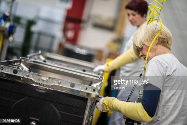 factory worker tightening the screws on product - inserting stock pictures, royalty-free photos & images