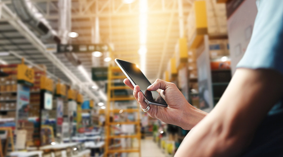 Factory worker using application on mobile smartphone to operate automation for modern trade. Checking order in large warehouse. Import and export the shipping cargo. 1023224312