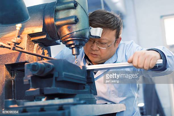 Factory worker using drilling machine