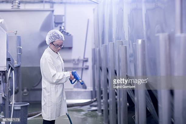 factory worker using water spray gun - sigrid gombert stock-fotos und bilder