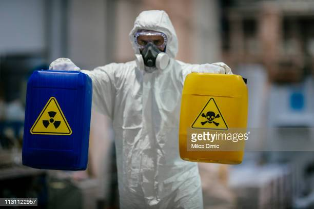 factory worker wearing gas mask and radioactive protection suit - danger stock photos and pictures