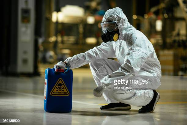 factory worker wearing gas mask and radioactive protection suit - toxin stock pictures, royalty-free photos & images