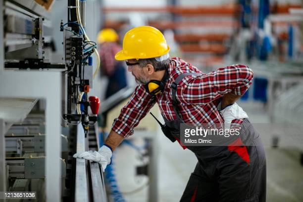 factory worker with painful back injury stock photo - physical injury stock pictures, royalty-free photos & images
