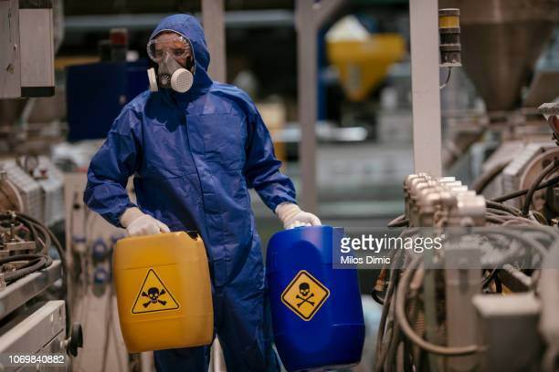 factory worker working with dangerous materials - toxin stock pictures, royalty-free photos & images