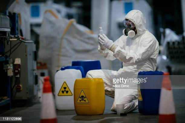 factory worker working with dangerous materials - hazmat stock pictures, royalty-free photos & images