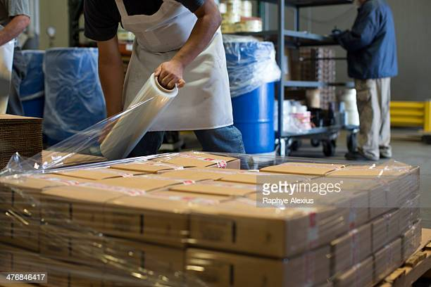 Factory worker wrapping cardboard boxes with clingfilm