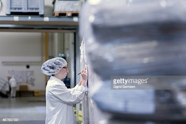 factory worker writing on paperwork - sigrid gombert stock-fotos und bilder
