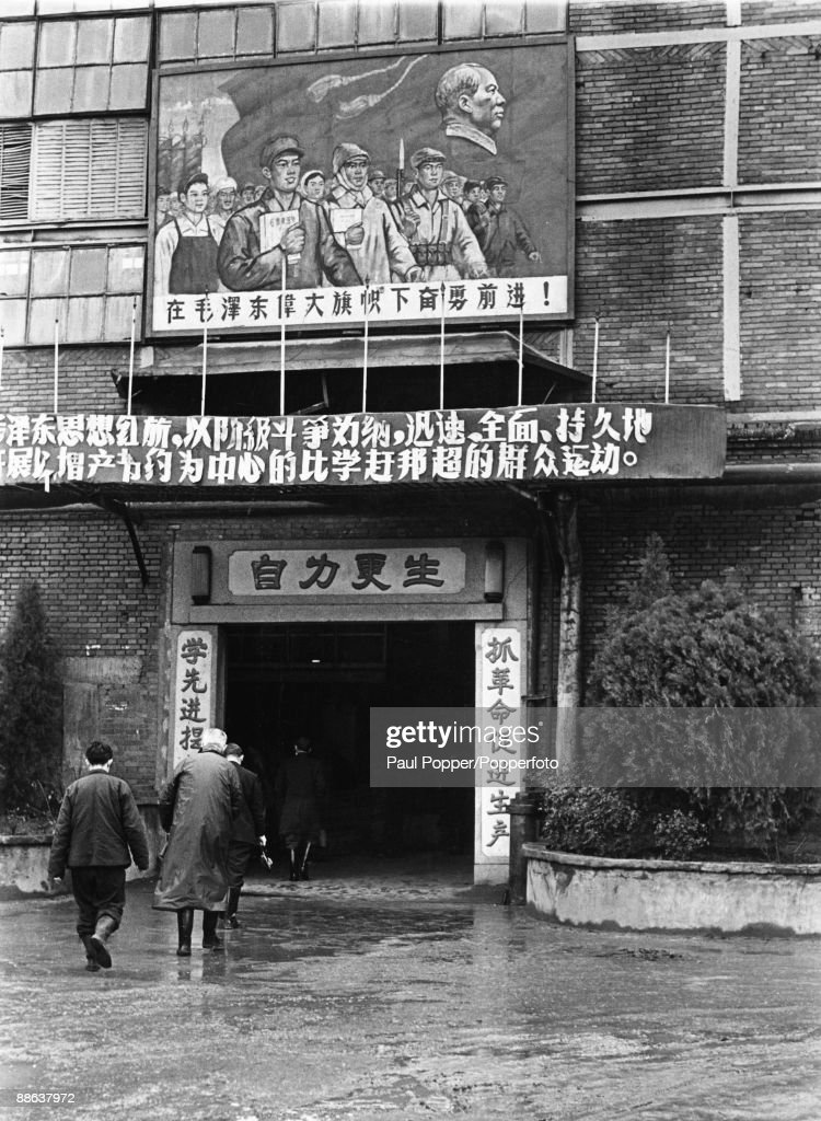 Factory workers arrive at the Wuhan Iron and Steel works in China, circa 1958. The sign above the entrance reads 'Advance beneath the mighty banner of Mao Tse Tung!'