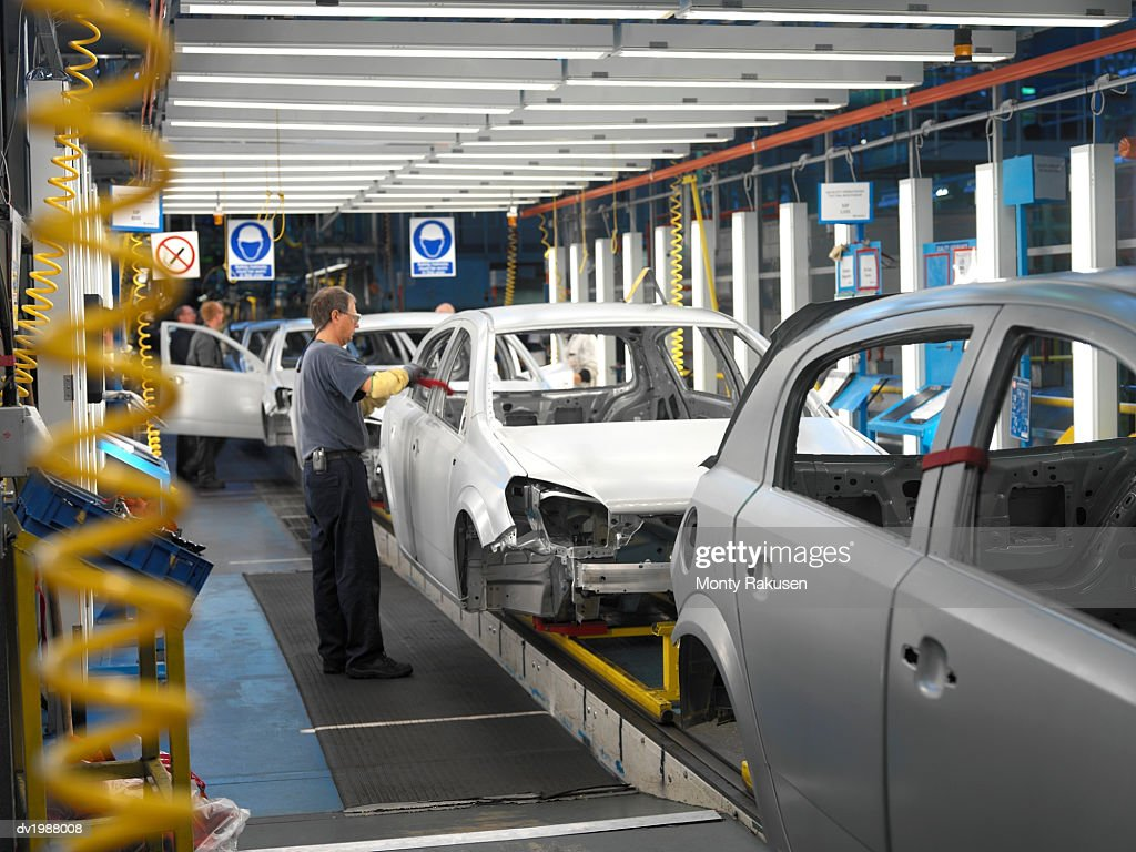 Factory Workers Assembling Cars in a Factory : Stock Photo