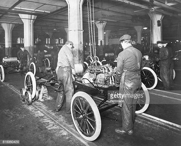 Factory workers at the Ford Motor Company plant assemble a Model T automobile