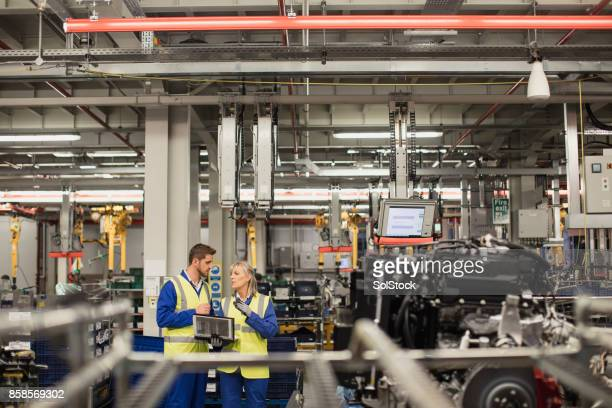 factory workers discussing on the production line - wide shot stock pictures, royalty-free photos & images