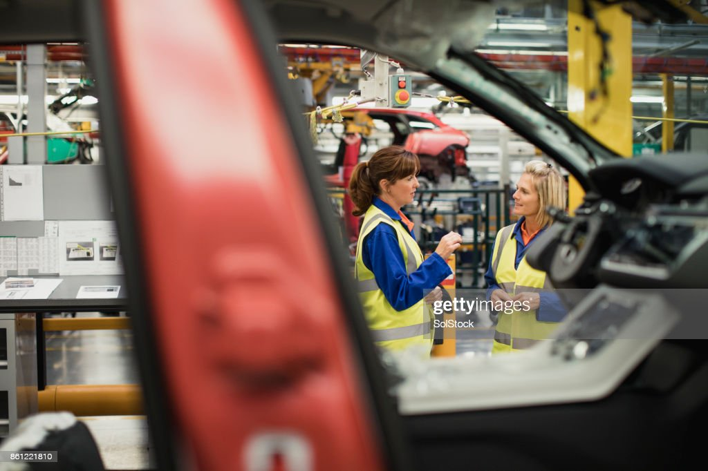 Factory Workers Discussing on the Production Line : Stock Photo