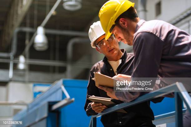 factory workers discussing with each other in factory - industrieberuf stock-fotos und bilder