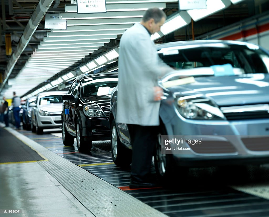 Factory Workers Inspecting Cars on an Assembly Line : Stock Photo