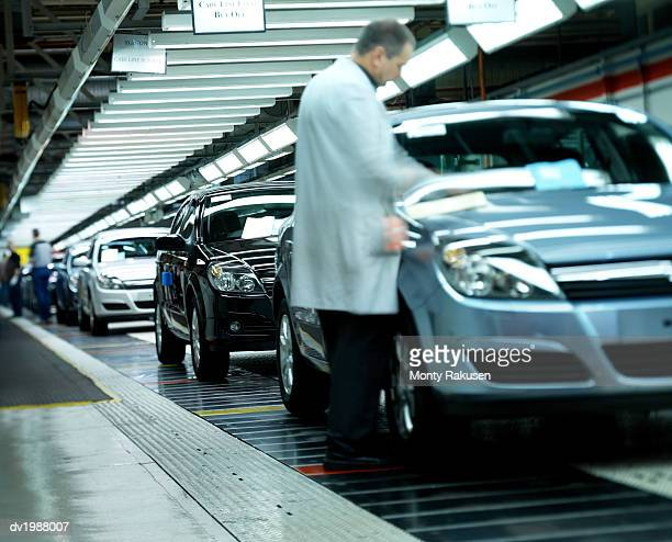 Factory Workers Inspecting Cars on an Assembly Line