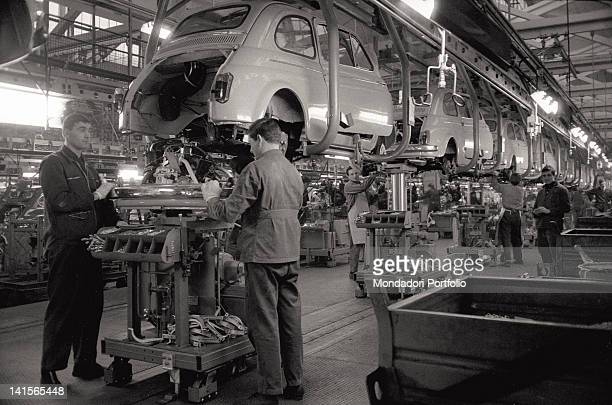 Factory workers of FIAT are at work in a warehouse of a manifacturing plant in Turin They assemble the motor of a FIAT Cinquecento put up form hearth...