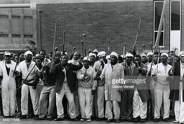 Factory workers raise sticks and clubs in protest during a workers strike outside a factory in Durban, South Africa.