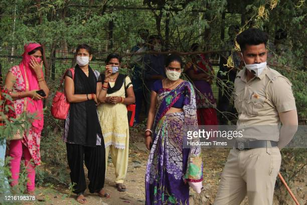 Factory workers seen at Delhi-Gurugram border after they were stopped by the Haryana Police, near Udyog Vihar, these workers trek through the forest...