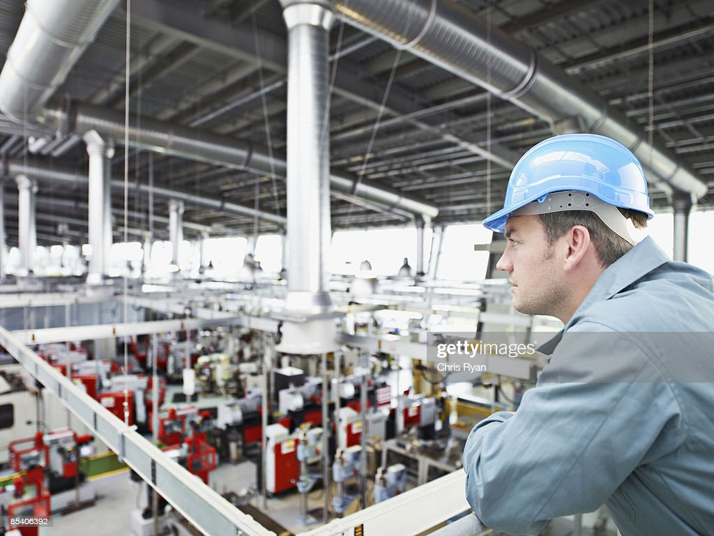 Factory-worker in hard-hat looking at factory floor : Stock Photo