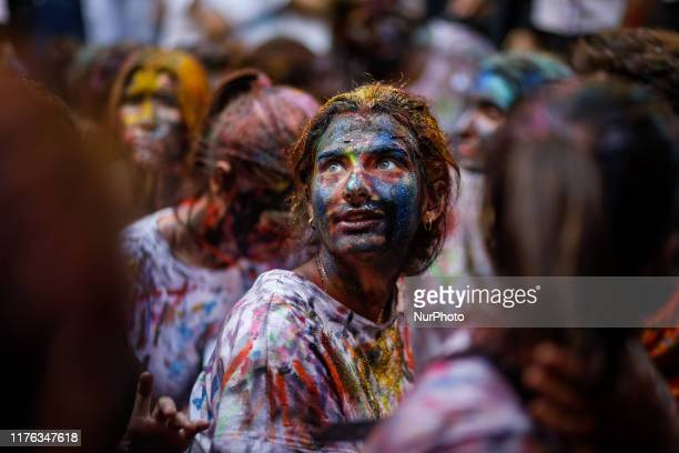 Faculty of medicine first year students walk down a hall while seniors paint them with different color paints and glitter as part of an annual...
