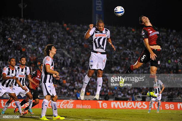 Facundo Erpen of Atlas heads the ball over the mark Lucas Silva of Monterrey during a match between Monterrey and Atlas as part of 10th round...