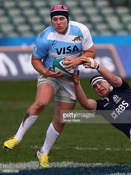 Facundo Gigena of Argentina beats the tackle of James Malcolm of Scotland during the 2014 Junior World Championship match between Argentina and...